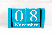 November 8th. Blue cube calendar with month and date on wooden background.