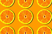 Sliced oranges pattern on bright orange background, minimal concept