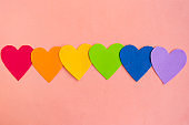 Hearts in lgbtq colors on pastel pink background, top view