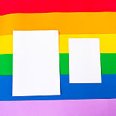 Two white mockup blanks on LGBTQ colors flag, top view, copy space for the text