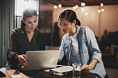Diverse businesswomen working together on a laptop in an office