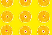 Sliced oranges pattern on yellow background, minimal concept