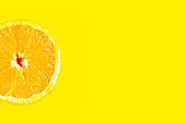 Sliced fresh sweet orange on bright yellow background, minimal concept, copy space for the text, banner