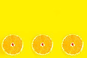 Sliced fresh sweet oranges on bright yellow background, minimal concept, copy space for the text, banner
