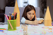 One little girl surrounded by plastic toy animals and wooden geometric figures drawing with pencils