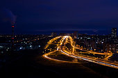 night city landscape with illuminated road junction, industrial and residential buildings
