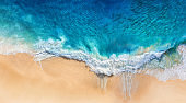 Beach and waves as a background from top view. Blue water background from drone. Summer seascape from air. Travel image