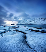 Haukland beach, Lofoten islands, Norway. Landscape with long exposure shot. Mountains, beach and clouds. Winter landscape near the ocean. Norway - travel