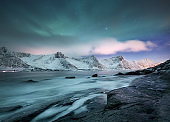 Aurora borealis on Lofoten islands, Norway. Green northern lights above mountains. Night winter landscape with aurora. Natural background in the Norway.