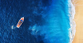 Seascape with beach and boat. Yachts at the sea surface. Aerial view of luxury floating boat on blue Adriatic sea at sunny day. Travel - image