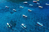 Boats in the blue lagoon. Aerial view of floating boat on transparent turquoise water at sunny day. Top view from drone. Seascape with motorboat in bay. Travel - image