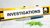 Text Investigations on the folder that is located on the financial reports with blue pen and green paper clips