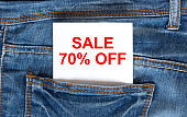 Text Sale 70 off on white paper in the pocket of blue denim jeans