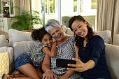 Mixed race woman with her senior mother and her young daughter taking a selfie