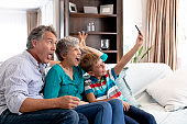 Senior Caucasian couple and their grandson taking a selfie at home