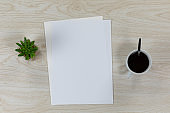 White sheet of papers surrounded by a plant and coffee on wood table
