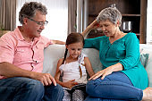 Senior Caucasian couple watching a family album at home with their granddaughter
