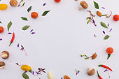 Fresh vegetables and leaves arranged in circle on white background