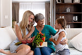Senior Caucasian woman spending time with her daughter and her granddaughter at home