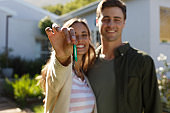Smiling caucasian couple in garden showing keys to camera
