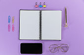 View of a black smartphone, a notebook, a pen, glasses and paperclips on plain purple background