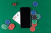 View of a black smartphone, playing cards, a red dice and colorful tokens on plain green surface