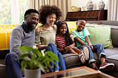 Mixed race family spending time together sitting on a couch