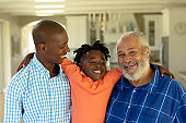 African American man standing with his senior father and his young son