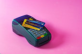 Credit card and credit card scanner on a pink background