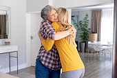 Senior Caucasian woman and her adult daughter embracing and smiling at home