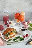 Festive breakfast table with croissant sandwich, fried egg and asparagus.