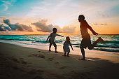 happy father with kids jumping from joy at sunset beach
