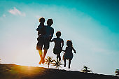 happy father with kids jumping from joy at sunset