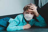 Sick child with infection or virus, boy wearing mask on quarantine at home