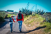 father and son walk on road in Canary islands, Spain