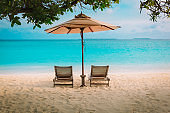 Two beach chairs on tropical sea vacation
