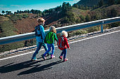 kids travel by road in mountains, family vacation in nature