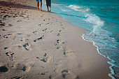 mother and son walking on beach leaving footprint in sand