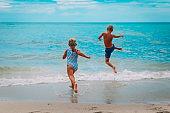 happy boy and girl run swim on beach