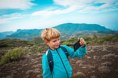 little boy making selfie while travel by in mountains