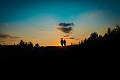 Silhouette of happy boy and girl run at sunset