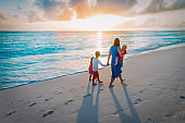 mother and kids walking on beach at sunset