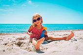 sun protection - cute little girl with suncream at beach