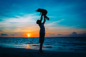 Father and little daughter silhouettes play at sunset beach