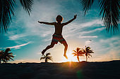 happy boy enjoy sunset on tropical beach with palm trees