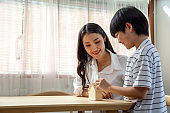 Asian mother and son putting coins into bank home model, Saving money concept