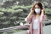 Asian woman wearing a protective face mask for plague coronavirus. Facial hygienic mask for safety outdoor environmental awareness or virus spread concept