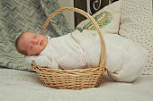 A newborn baby in a white blanket sleeps sweetly in a wicker basket on a bed in a bedroom at home. Family concept, home birth, new life.