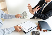 Businessman rejecting money or refusing money form of dollar bills to take the bribe to agreement contract, anti bribery and corruption concept