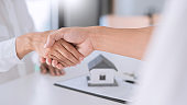 Estate agent in suit sitting in an office desk shaking hands with customer after contract signature accept agreement finish buying or rental real estate for transfer right of property